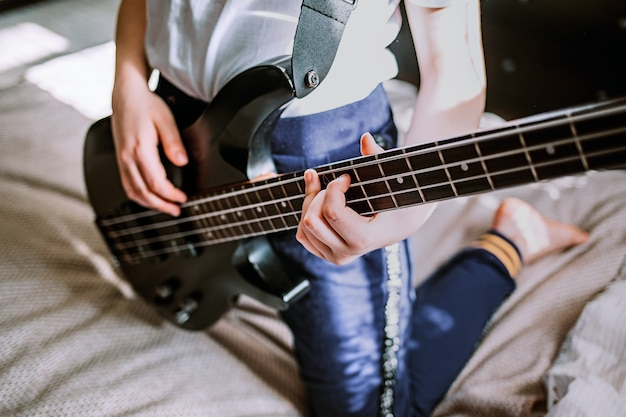 ベースギターを弾く女性をクローズアップ