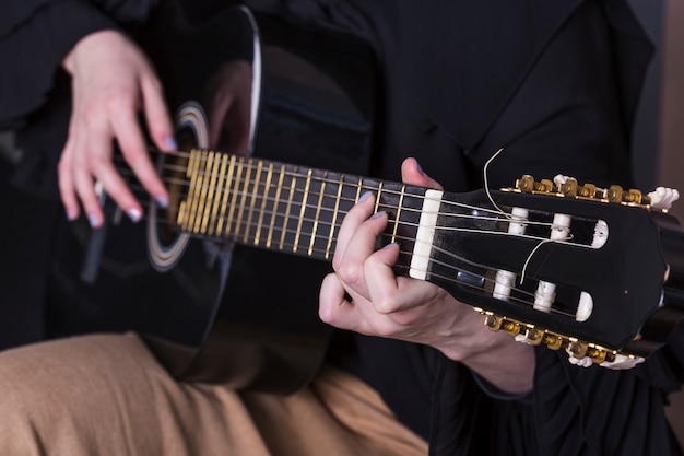 Close up of woman playing on the guitar