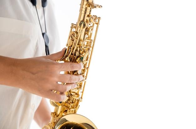 Закройте вверх по женщине, играющей на саксофоне, изолированной на белом фоне студии. вдохновленный музыкант, детали художественного занятия, мировой классический инструмент для джаза и блюза. понятие о хобби, творчестве. листовка