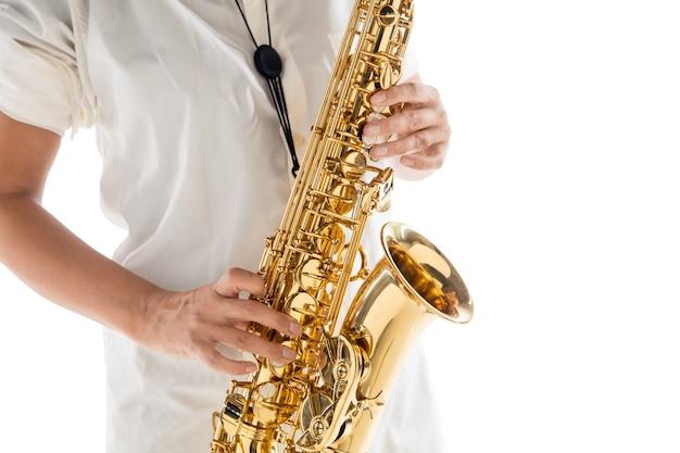 흰색 스튜디오 배경에 격리된 색소폰을 연주하는 여자를 닫습니다. 영감을 받은 음악가, 예술 직업에 대한 세부 정보, 재즈와 블루스를 위한 세계 클래식 악기. 취미, 창의성의 개념입니다.