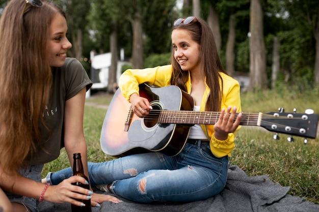 Крупным планом женщина играет на гитаре на открытом воздухе