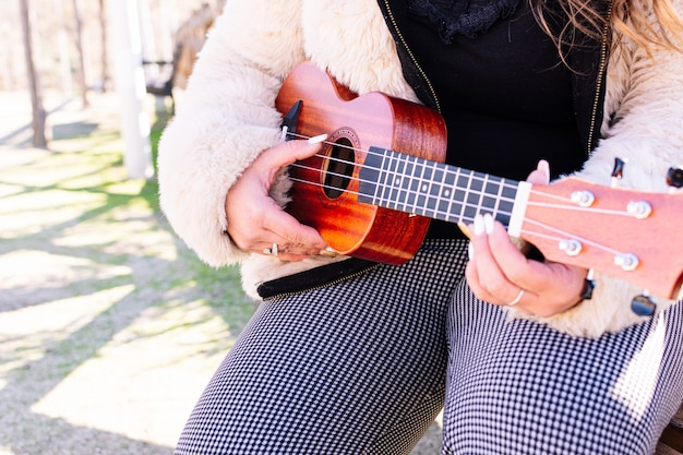 Close up of a woman playing the ukulele in a park