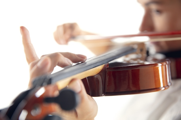 Закройте вверх по женщине, играющей на скрипке, изолированной на белом фоне студии. вдохновленный музыкант, детали художественного занятия, мировой классический инструмент. понятие о хобби, творчестве, вдохновении.