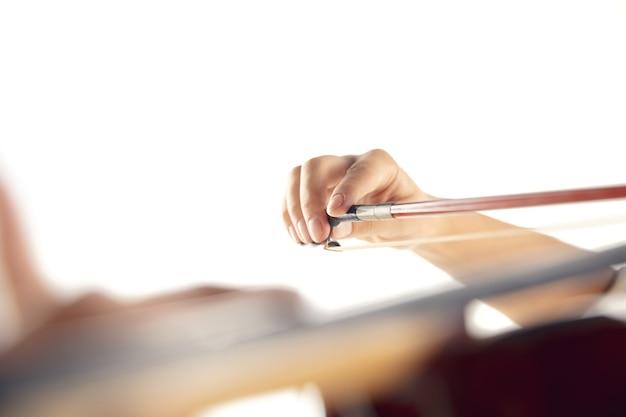 흰색 스튜디오 배경에 격리된 바이올린을 연주하는 여자를 닫습니다. 영감을 받은 음악가, 예술 직업의 세부 사항, 세계 클래식 악기. 취미, 창의성, 영감의 개념.