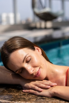 プールでポーズをとって女性をクローズアップ