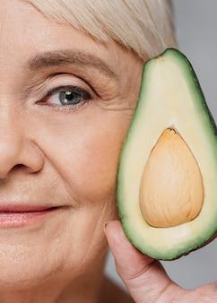 Donna del primo piano che posa con l'avocado