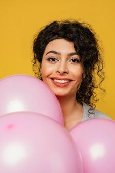 Donna del primo piano in posa con palloncini