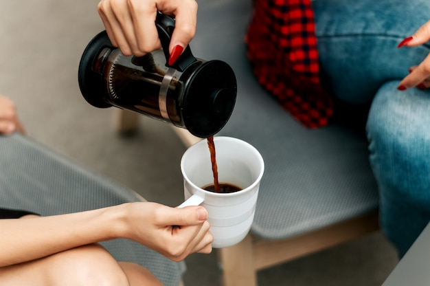 Close up of woman pouring coffee into cup.