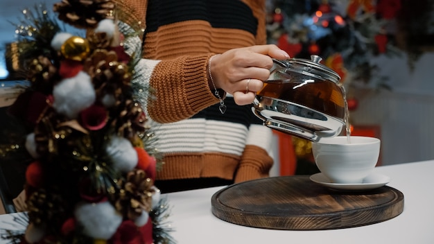 Close up of woman pouring cup of tea from kettle at home