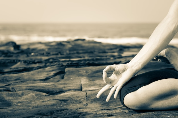 Close up of a woman practicing yoga on the rocks by the sea in goa, india. yogi on the beach. meditation, mindfulness, nature connection concept
