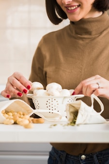 自家製キノコを準備するクローズアップの女性
