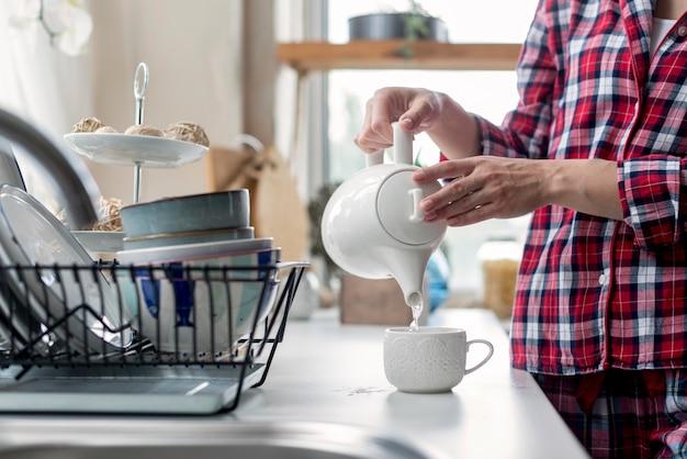 Donna del primo piano che prepara tè