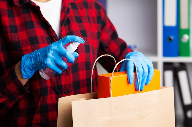 Close up of woman in protective gloves disinfecting shopping