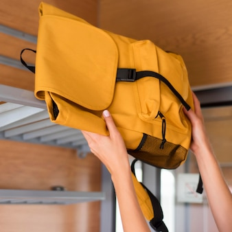 Close-up woman putting backpack on train rack