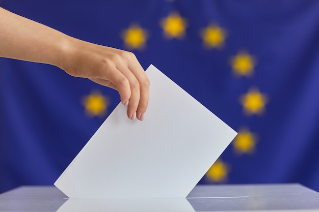 Close-up of woman putting the envelope into the box she voting for new president