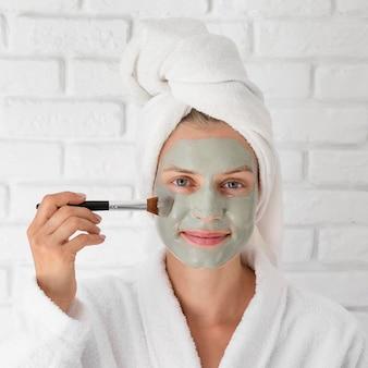 Donna del primo piano che mette sulla maschera facciale verde
