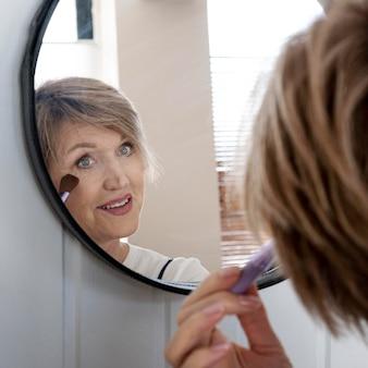Крупным планом женщина, наносящая макияж