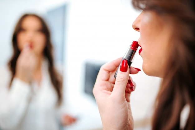 Close-up of woman putting red lipstick.