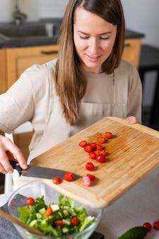 Chiuda sulla donna che mette i pomodori in insalata
