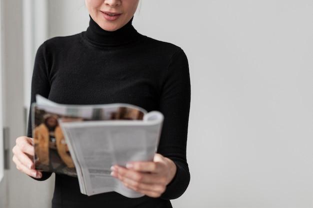 Close-up woman reading magazine