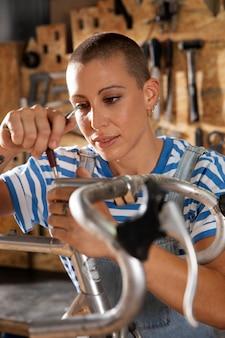 Primo piano donna che ripara la bici
