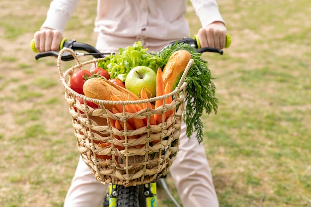Close-up woman riding bike with groceries
