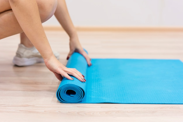 Close-up woman rolling fitness mat