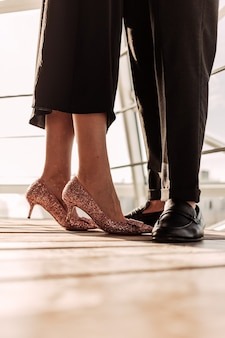 Close up a woman in rose golden high heels staying together with her man in black shoes.