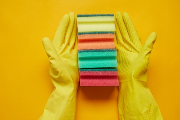 Close-up of woman in rubber gloves holding colorful sponges in a row isolated