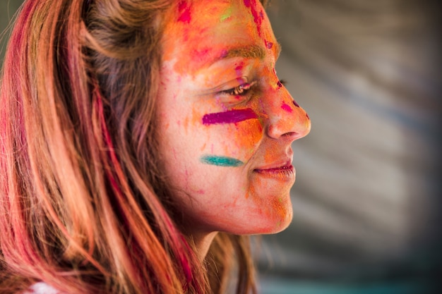Close-up of woman's face covered with holi color