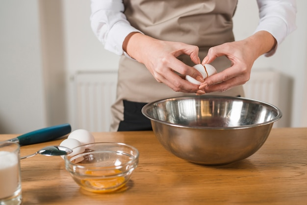Close-up of woman's hand breaking an egg in the mixing bowl on wooden table