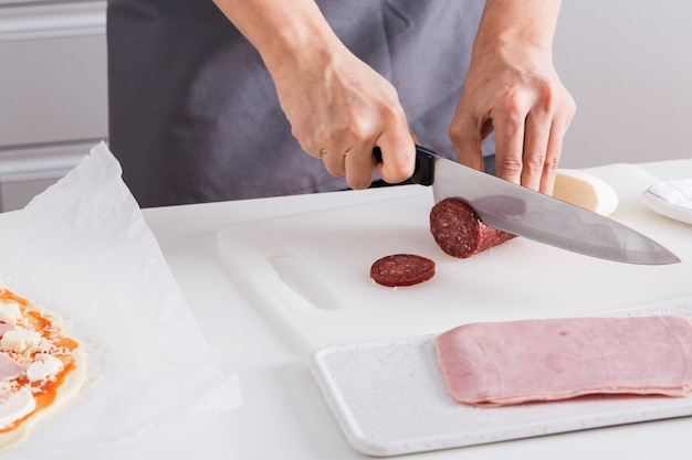 Close-up of woman's hand cutting the salami slices with sharp knife on chopping board