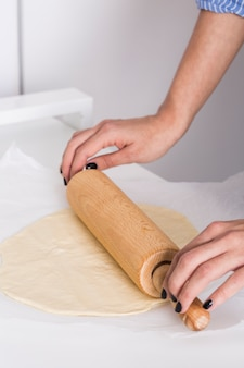 Close-up of a woman's hand flattening the dough with rolling pin on parchment paper