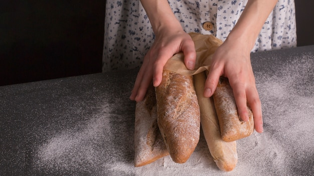 Close-up of woman's hand holding baked breads on kitchen counter