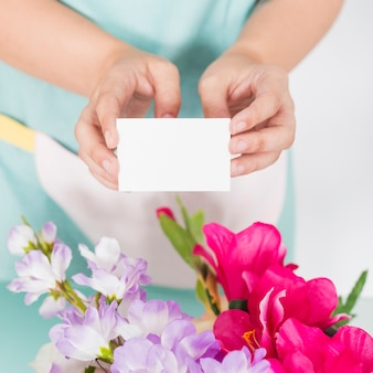 Close-up of a woman's hand holding blank visiting card over colorful flowers