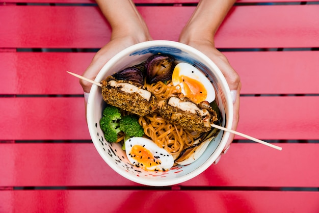Close-up of a woman's hand holding bowl of ramen noodles with egg; onion and broccoli on red
