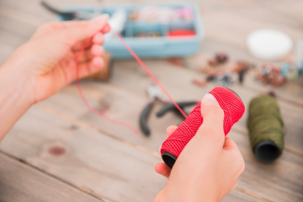 Close-up of a woman's hand holding bright red yarn over the blurred desk