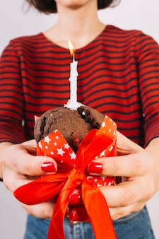 Close-up of a woman's hand holding cake with ribbon and glowing candle