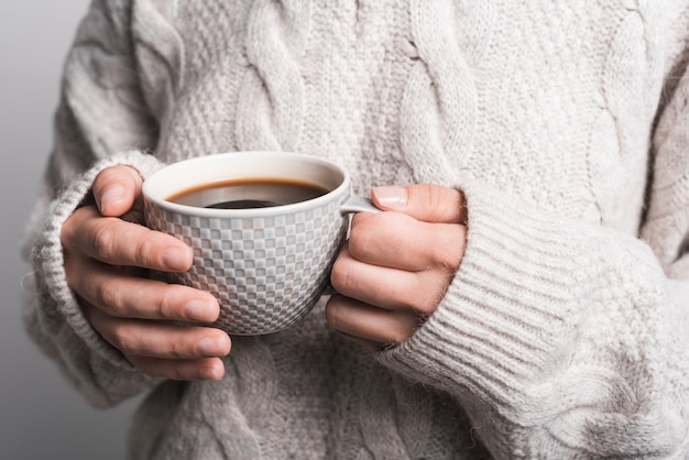Close-up of woman's hand holding coffee cup