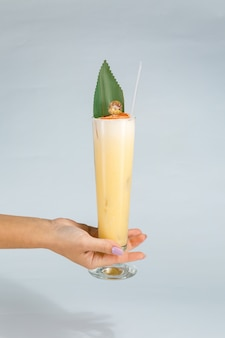 Close up of a woman's hand holding a glass of tropical pina colada cocktail on white  with copy space. summer time vacation concept.