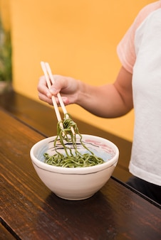 Close-up of woman's hand holding green seaweed salad with chopstick on wooden table