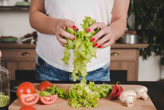 Close-up of woman's hand holding lettuce in hands over chopping board
