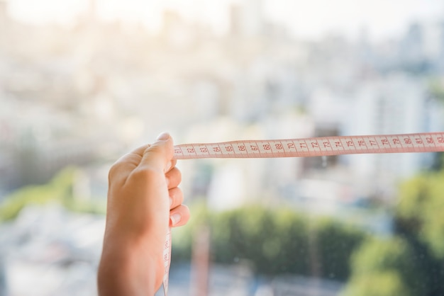 Close-up of woman's hand holding measuring tape against blurred backdrop
