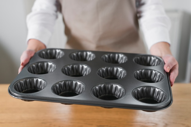Close-up of woman's hand holding metal muffin cupcake tray pan
