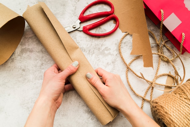 Close-up of woman's hand holding rolled up brown paper