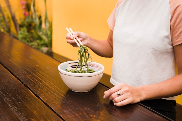 Close-up of a woman's hand holding seaweeds with chopsticks over wooden desk