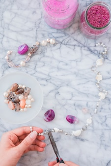 Close-up of woman's hand making beads jewelry with plier on marble textured background