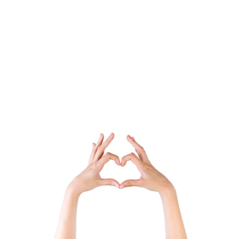 Close-up of a woman's hand making heart shape over white backdrop