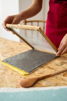 Primo piano della mano di una donna che fa carta con polpa