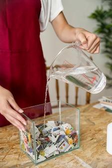 Primo piano dell'acqua di versamento della mano di una donna su carta lacerata in contenitore
